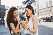 Smiling Woman Showing Mobile Phone To Her Female Friend Outdoors