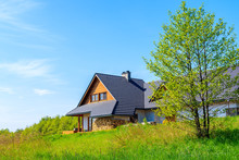 Side View Of A House On Green Meadow During Spring In Countryside Landscape Near Krakow City, Poland