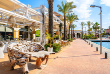 Restaurant Tables With Chairs In Beautiful Sotogrande Marina With Colorful Houses And Palm Trees On Coastal Promenade, Costa Del Sol, Spain