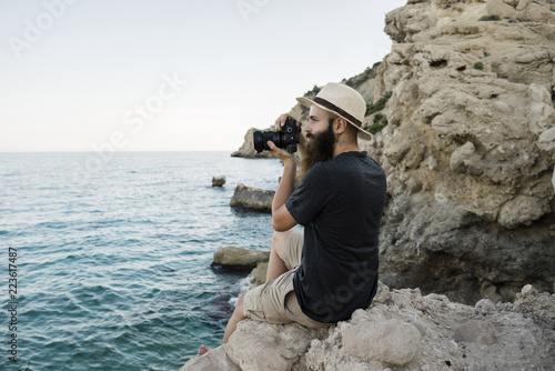 Side view of bearded tourist photographing with camera while sitting on rocks against clear sky
