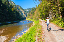 Young Woman Cycling Along Dunajec River On Sunny Autumn Day, Pieniny Mountains, Poland