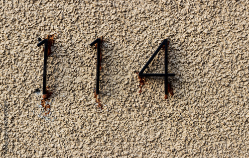 Tela  Old grungy white rock wall with the numbers 114 hastily glued
