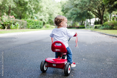 39aba8c5583 Young Child Toddler Profile on Red Tricycle on a Neighborhood Street ...