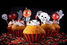 Happy Halloween Muffin Cupcakes With Funny Party Decorations Set Against A Black Background With Differential Focus And Creative Lighting.