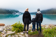 Young Family Admiring The View At Lake Louise On A Foggy Day