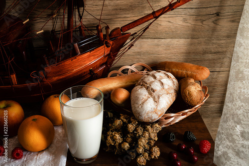 still life of breakfast set of milk variety kinds of bread in basket and fruits on wooden table near lace curtain by window
