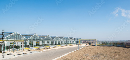 Fotobehang Industrial geb. panorama and appearance of the greenhouse in the day time. facade and glass roof of hothouse