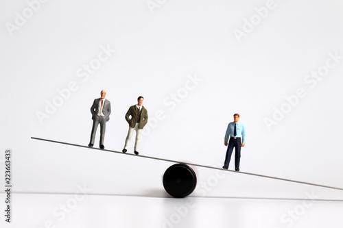 Obraz na plátně  Miniature men standing on the seesaw.
