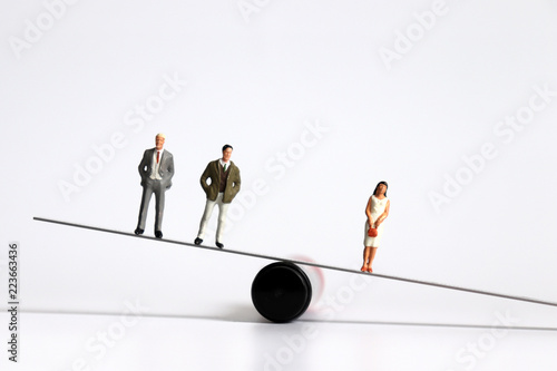 Fotografia, Obraz  Two miniature men and a miniature woman standing on the seesaw.