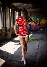 Beautiful Young Woman In A Short Dress Holding An Ax In Abandoned Building