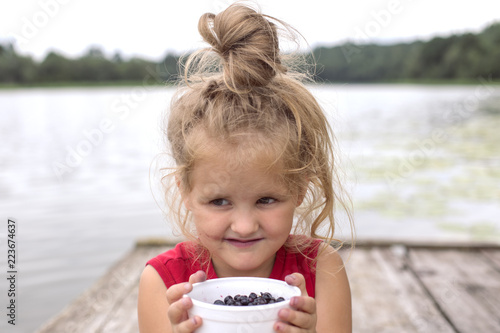 Girl holding a plate of blueberries near the face