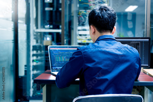 Tableau sur Toile Young IT engineer working at server room is Multi Display, Data Protection Security Privacy Concept