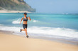 young happy and attractive sport runner woman doing running workout sprinting on tropical paradise beach showing fit and athletic body in wellness fitness concept