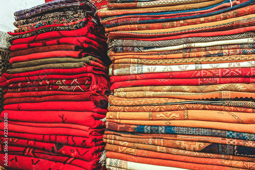 A pile of neatly folded, beautiful hand woven berber rugs