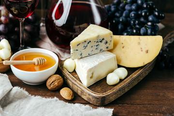 Ser i wino, karafki i okulary, drewniane tło, zakąska, winogrona