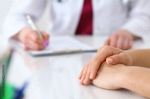 Fototapety, obrazy: Doctor woman consulting patient while filling up an application form at the desk in hospital. Just hands close-up. Medicine and health care concept