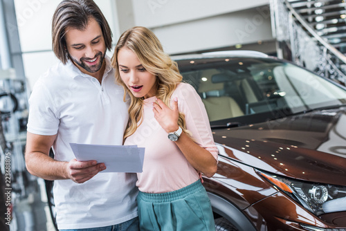 portrait of couple with catalog choosing car at dealership salon