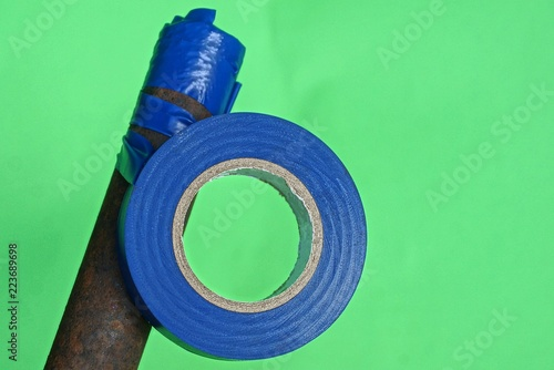 Photo  a hank of blue electrical tape wound on a rusty brown rod on a green background