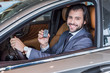 happy businessman showing car key while sitting in new car in dealership salon