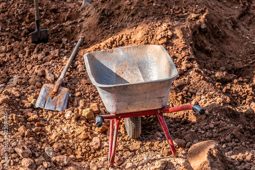 Fotografía  metal wheelbarrow with red handles standing at construction site