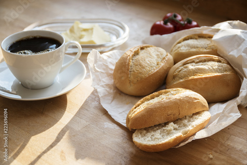 bread rolls or buns in a white paper bag, tomatoes, butter and a cup of coffee for breakfast on a wooden table