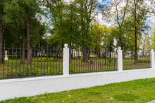 Metal Fence With White Concrete Pillars In The City Park. Autumn Day.