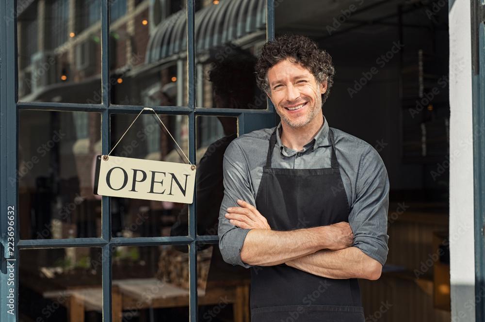 Fototapeta Owner standing outside restaurant