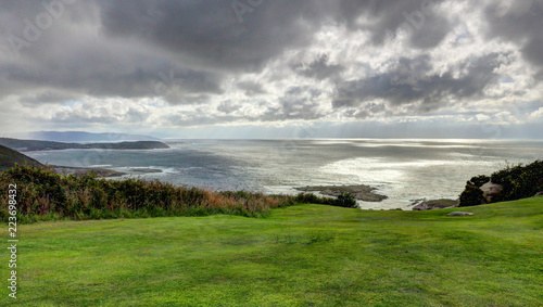 A landscape of a cloudy stormy sea and a grass lawn from Parque de Bens in Galicia capital city La Coruña