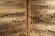 canvas print picture - An old score written on a parchment, showing a few staves with notes and a miniature, for a song in Latin