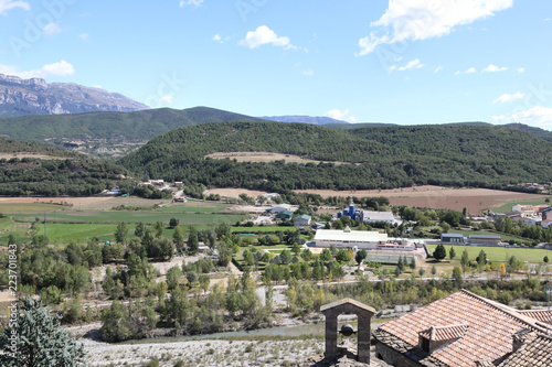 A landscape of the Pyrenees mountains with green forests and a blue sky with some clouds in the Aragonese small rural town Ainsa, Spain