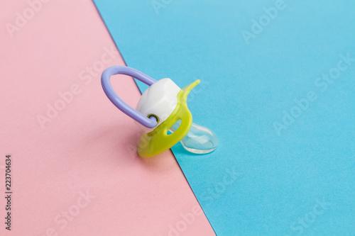 Fototapeta Chupete de bebe sobre fondo liso rosa y celeste