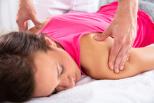 Therapist Giving Shoulder Massage To Female Patient