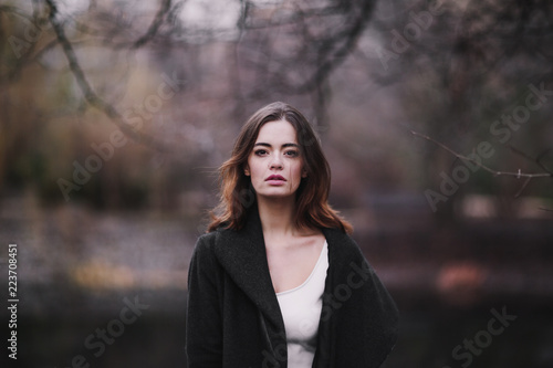 Carta da parati Attractive charming young woman in a white cotton dress and dark coat walking in the autumn park