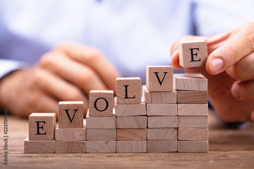 Fototapeta Person's Hand Placing Last Alphabet Of Word Evolve