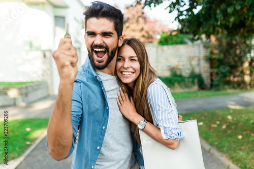 Happy young couple with key  in hand standing outside in front of their new home Canvas-taulu