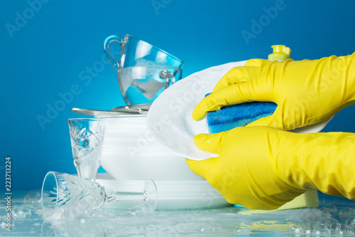 Hands in yellow gloves wash blue sponge plate on light blue background