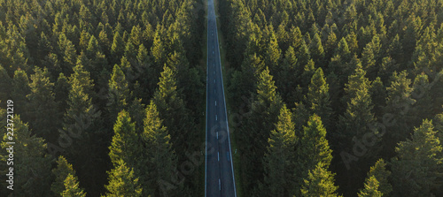 Valokuva  Aerial view from above of country road through the green forest