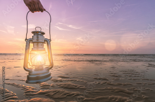 hand holds vintage lantern at the beach at sunset. copyspace for your individual text.