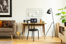 Black, Wooden Chair And An Industrial Floor Lamp By A Vintage Desk With A Laptop In A White Living Room Interior