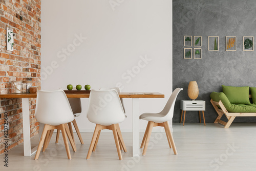 Fotomural  Wooden dining table and chairs by an exposed brick wall in a bright and natural
