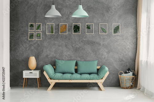Foto  Wooden sofa with mint green cushions by a gray wall with a botanic gallery in a