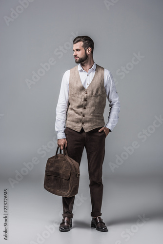 Slika na platnu stylish elegant man in waistcoat posing with leather bag on grey