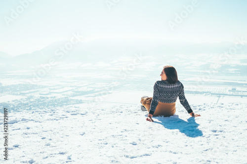 Woman sits on the snowy mountain hill over the city. Sunny winter beautiful weather day