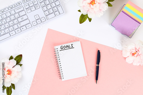 Photo  Write a goal for the new year 2010 in a white notebook on a white desktop next to a coffee mug and a keyboard