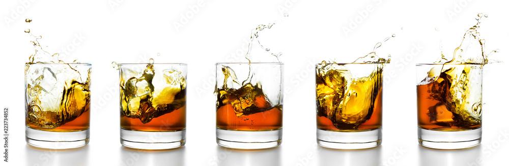 Fototapeta Scotch glasses with whiskey splashing from them