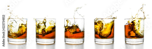 Scotch glasses with whiskey splashing from them