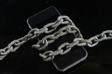 Chains Were Wrapped On A Mobile Phone With A Dark Background.