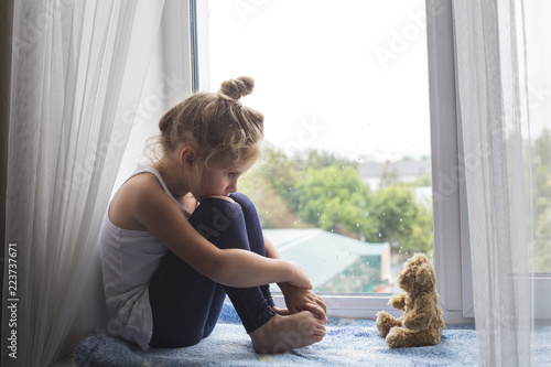 Sad litttle girl sits on a window sill and looks at a bear