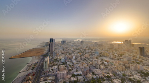 Fotografie, Obraz  Sunrise and morning with Cityscape of Ajman from rooftop timelapse