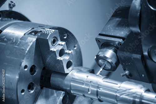 The CNC lathe machine cutting  the groove slot at the steel shaft by milling spindle Canvas Print